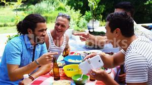 Smiling man showing his mobile phone to his friends while having meal outdoors