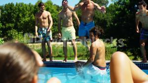 Group of friends jumping in the swimming pool