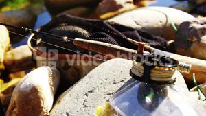 Fly fishing rod, reel and tackle box on rock