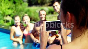 Smiling woman clicking photos of friends from mobile phone near poolside