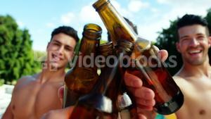 Group of male friends toasting beer bottles at poolside