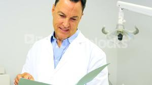 Portrait of smiling dentist looking at file