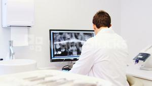 Attentive dentist examining x-ray report on computer