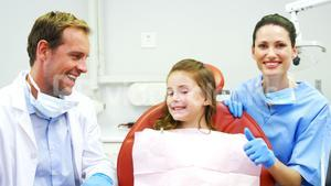Portrait of smiling dentists and young patient showing thumbs up