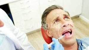 Scared man receiving injection from dentist