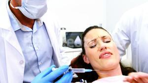 Woman stopping dentist for examining her in clinic