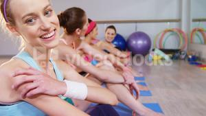 Beautiful woman smiling while her group talking in background in fitness studio