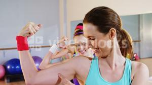 Group of smiling fit women showing her muscle