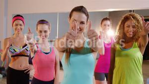 Group of smiling fit women showing thumbs up