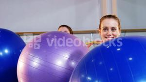 Three women exercising with fitness ball