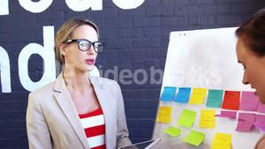 Executives discussing over white board