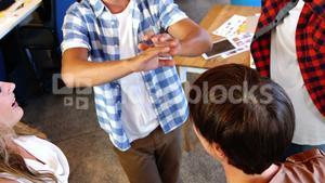 Executives giving high five and forming huddle in office