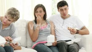 Teenagers eating burgers and fries on the sofa