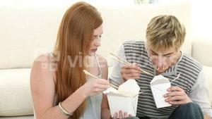 Couple of teenagers eating pasta on the floor