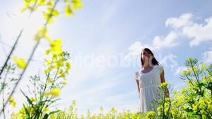 Happy young woman with arms outstretched standing in field