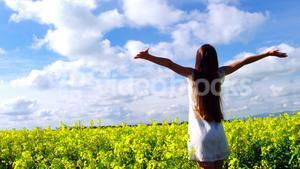 Young woman with arms outstretched standing in field