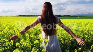 Woman touching flowers while walking in field