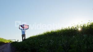 Man holding american flag and running in field