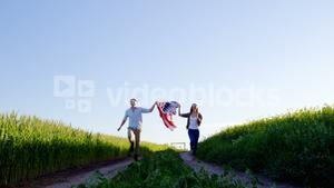Couple holding american flag and running in field