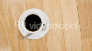 Black coffee served in white cup on wooden plank