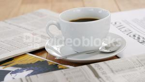 Newspaper and black coffee on table