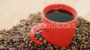 Black coffee surrounded with roasted beans