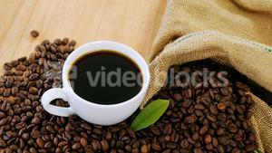 Coffee cup with coffee beans and leaf
