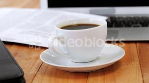 Coffee cup with file folder and laptop