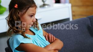 Sad girl sitting with arms crossed in living room