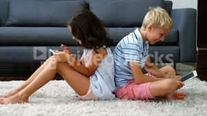 Siblings sitting back to back and using digital tablet in living room
