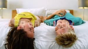Siblings relaxing on bed in bedroom