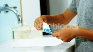 Boy putting tooth paste on brush in bathroom