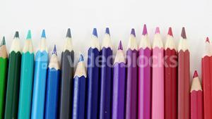 Close-up of colored pencils arranged in a wave pattern
