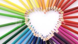 Colored pencils arranged in heart shape on white background
