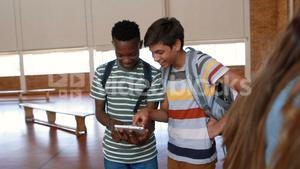 Happy students using digital tablet in basketball court