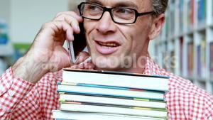 Male teacher talking on mobile phone in library