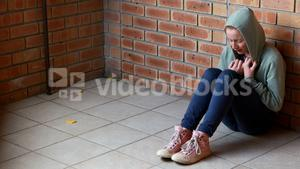 Sad schoolgirl sitting alone on floor