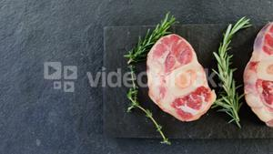 Sirloin chops and rosemary on chopping board