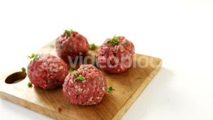 Raw meat balls on wooden board