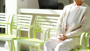Thoughtful senior woman sitting on chair in lobby