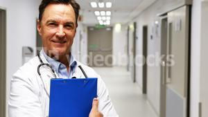 Portrait of doctor holding clipboard in corridor