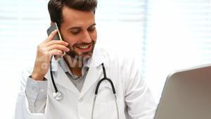 Male doctor talking on mobile phone while working on computer