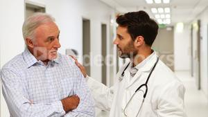 Doctor and patient discussing over clipboard in the corridor