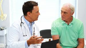 Doctor interacting with senior patient over a report