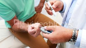 Mid-section of doctor examining senior patient blood sugar