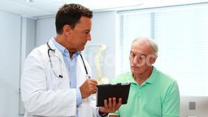 Doctor and senior patient discussing over digital tablet