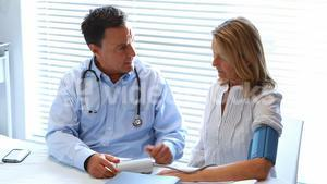 Doctor interacting with patient while checking blood pressure