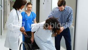 Man and doctors assisting pregnant woman to sit on wheelchair