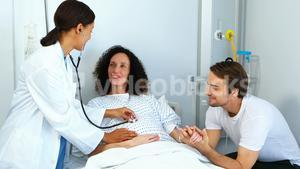 Doctor examining pregnant woman with stethoscope in ward