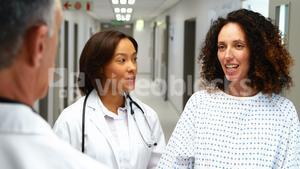 Pregnant woman interacting with doctors in corridor
